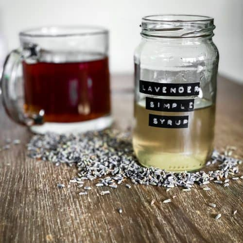 Lavender syrup for coffee with coffee cup behind it.