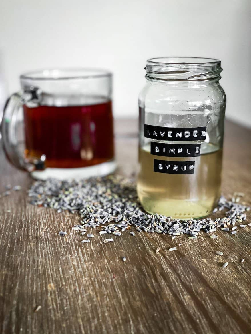 Lavender simple Syrup in jar. Coffee cup behind it all sitting on a bed of lavender buds.