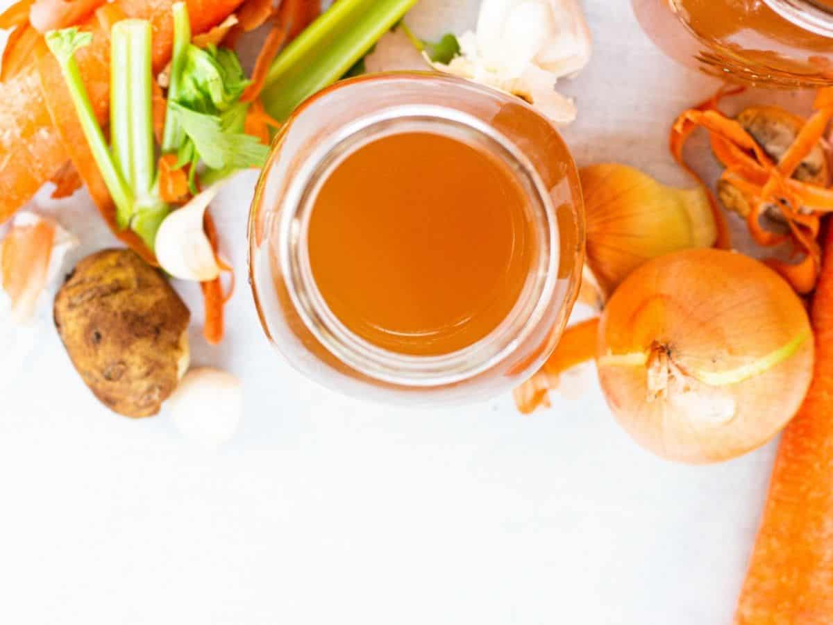 Top down view of vegetable broth in mason jar surrounded by vegetable scraps and peelings.