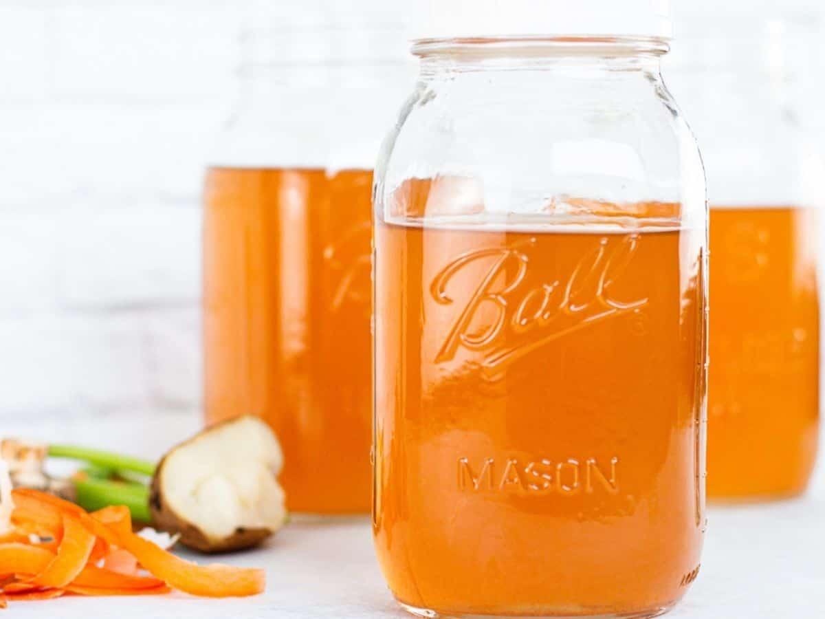 Vegetable broth in mason jars. Vegetable peeling to the side.