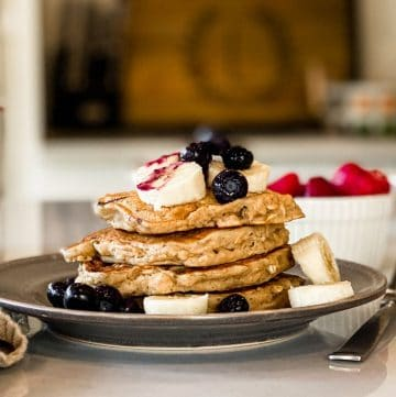 Stack of vegan oatmeal banana pancakes topped with blueberries, banana, syrup.