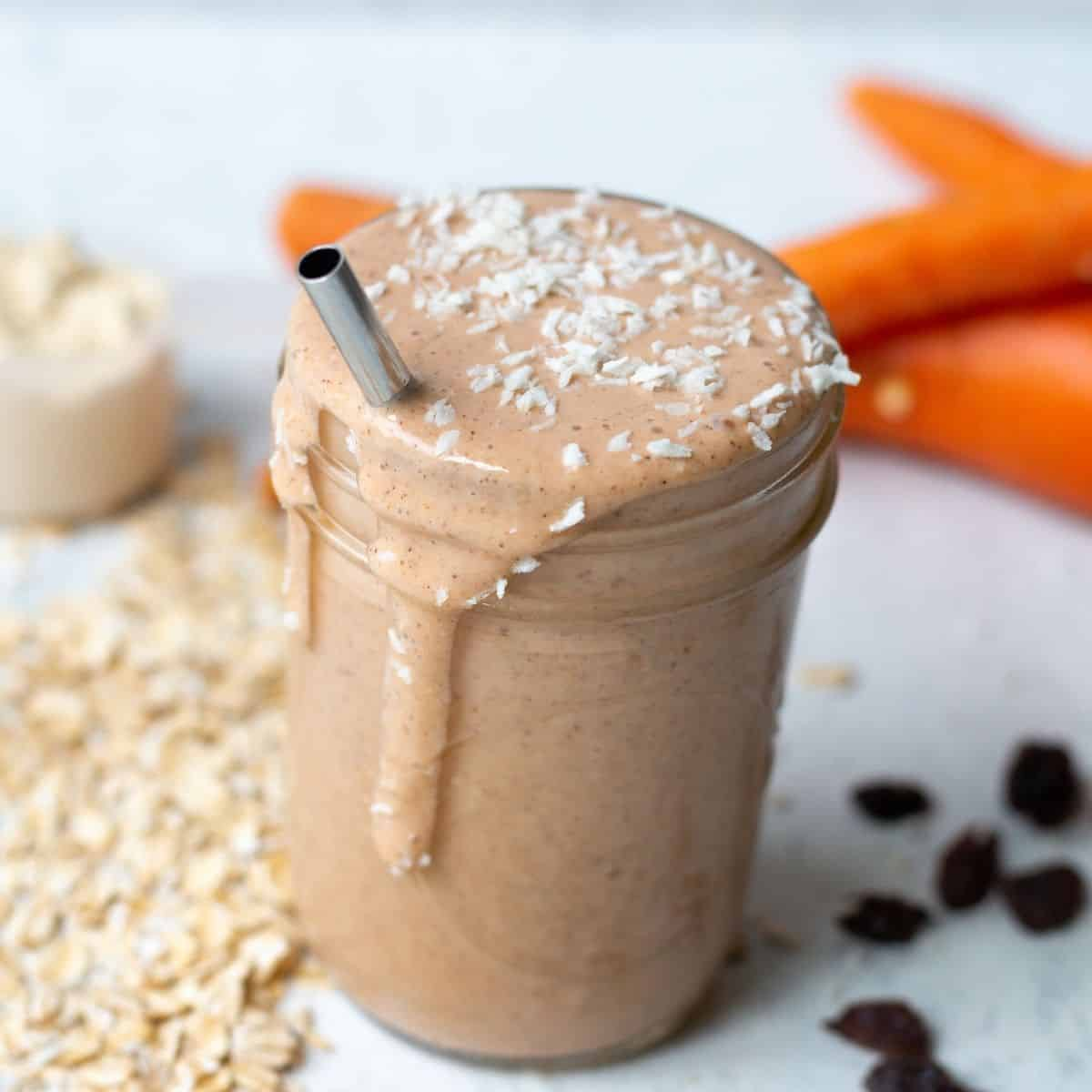 carrot banana smoothie in a mason jar with ingredients in the background. Topped with shredded coconut. metal straw in smoothie.