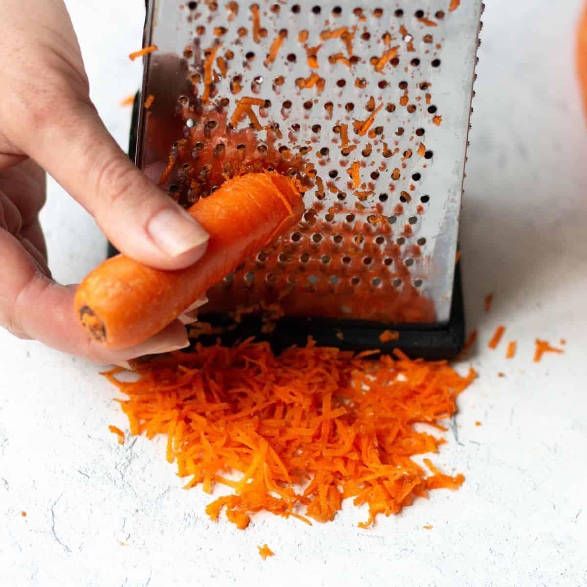 shredding carrots on a box grater