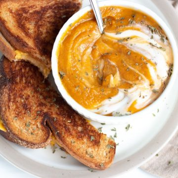 Pumpkin and sweet potato soup with sour cream swirled into it served with a vegan grilled cheese sandwich